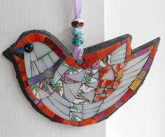 This little bird is made using the medium of mosaic and is on a slate base and is designed to hang up. The bird is made using hand cut stained