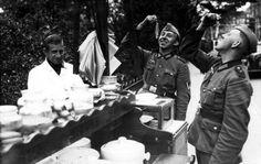 Tweede Wereldoorlog, haringkarren, haringen. Duitse soldaten smullen in Amsterdam van de Hollandse haring, een paar dagen na de inval. Nederland, Amsterdam, 16 mei 1940.