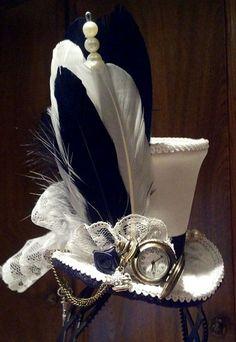 Inspirado en Alicia en el país de las maravillas mini sombrero de copa. Esta versión de color es de raso blanco con encaje blanco. Podemos trabajar con su esquema de colores también sin cargo. Plumas, pin de sombrero, abalorios y un bolsillo mini trabajo observan, hemos añadido llave victoriana en la cadena del reloj y un encanto de tetera y taza. El sombrero es en venda del pelo, pero puede ser cambiado a un clip de pelo.  Podemos trabajar con sus diseños personalizados, por favor…