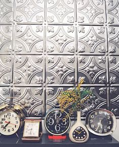 I have always loved the look of tin ceilings and walls. Painted or not, they add so much texture and such an unexpected jolt of design - Especially on the ceiling. I would love to have a somewhere I could incorporate tin. I love this idea with the alarm clocks, too. Eclectic without looking junky.