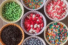 Colorful cupcake spinkles in bowls over a wooden table