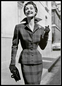 Sophie Malgat in classic tailored suit of green, purple and black plaid by Carven, brooch by Roger Scémama, black patent handbag by Prost, photo by Pottier, 1952