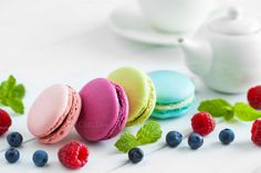 #Macaroons berries and teapot  Macaroons raspberries blackberries and teapot with cup of tea on background. Selective focus.