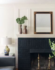 TRIM DESIGN CO. | Painting your brick fireplace black adds instant sophistication and drama to a living room or family room. Adding a large mirror to the mantel bounces and reflects light around the room keeping things light and airy. Adding color lamps and plenty of greenery keeps things fresh.   #trimdesignco #blackfireplace #paintedbrickfireplace