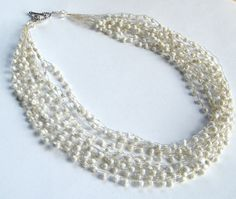 "White Beaded Necklace White Necklace White by BuddingCreations1, $35.00  This hand crocheted wire necklace is crafted with iridescent white glass seed beads. It has 9 randomly layered strands and has over 400 beads! And ends are finished with clear Swarovski Crystals on either side of the toggle clasp. It measures approximately 19"" and closes with a rhodium plated toggle."