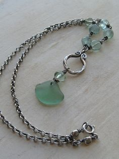 """Green Seaglass and Fluorite Necklace  The by valleybeadglassart. $45 Pale green fluorite stones wire-wrapped to sterling silver rolo chain and holds a fancy Hill Tribes silver twisted ring. A genuine piece of pale green seaglass topped with a fluorite stone is suspended from the ring. The 18"""" length closes with a spring ring clasp accented on each side with Hill Tribes silver 3-sided sun bead. The ring, seaglass and fluorite stone drop just under 2"""" from the chain"""