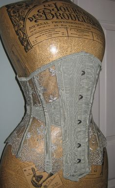 Sheer corset in lace and antique moire silk and used in the 19th century for women who wanted a slim waist and a lifted bust. There isn't a lot of material and color. This is because they hand made their corsets. Alissa Brooks-Johnson 4/5/16