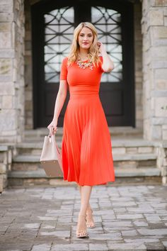 Pleated midi orange dress + statement necklace + nude strappy heels