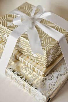 Various gold and white boxes stacked and tied together with white box