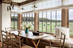 Industrial pendant lights from Rewire Gallery hang in a Martha's Vineyard, Massachusetts, breakfast nook, where the view is of bucolic surrounding farmland.