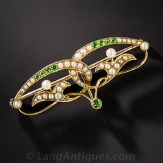 Art Nouveau Demantoid Garnet and Pearl Watch Pin. Sinuous, interlocking, mirror-image flowers bejeweled with shimmering seed pearls and vibrant yellowish-green demantoid garnets comprise this enchanting Art Nouveau brooch and/or watch pin, hand crafted in 15K yellow gold, hence of English origin - circa 1900. The loop on the back accommodates a pendant or pendant watch.