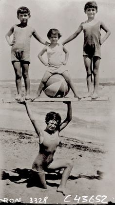 vintage everyday: Woman holding up children on the beach, 1931