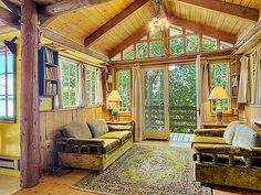 Vashon Island waterfront real estate for sale, living room with glass walls surrounded by trees and Puget Sound views