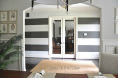 gray striped walls A bold, wide stripe on the walls makes a dramatic impact. Our foyer needed some pizzazz, so for an inexpensive fix (a can of paint) and cheap labor (me), I added a Striped Accent Walls, Striped Room, Paint Stripes, Wide Stripes, Striped Wallpaper Living Room, Sherwin Williams Gray, Sister Room, Painted Trays, Girl House