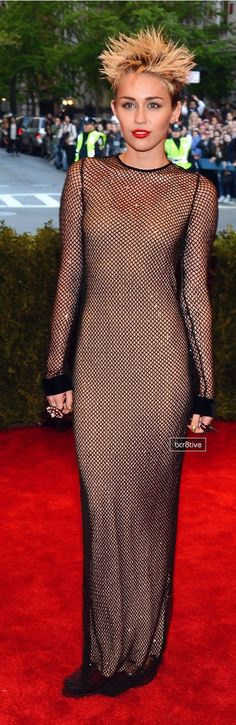 Miley Cyrus turned up the heat at New York's Metropolitan Museum of Art with spikey hair and a fishnet Marc Jacobs dress that gave the illusion she was nude underneath.