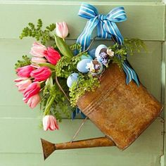 Greet guests with a front-door display of seasonal joys, such as this vintage watering can. Set floral foam in the can to secure the stems. Fill in with spring accents, then wire to door.