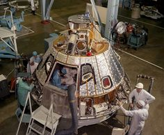 This high angle view shows the Apollo spacecraft Command Module for the AS-204 mission (later renamed Apollo 1), looking toward -Z axis, during preparation for installation of the crew compartment heat shield, showing mechanics working on aft bay.