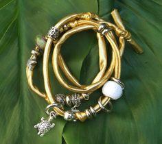Bracciale in lycra dorata. Charms in resina sintetica e charms in metallo color argento