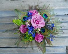 Peacock feathers with lavender roses, delphenium, bells of Ireland, waxflower, and hypericum berries