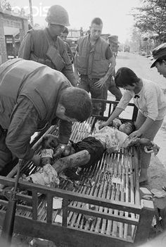 13 Mar 1968, Hue, South Vietnam --- Communist Mine Wounds Children. Hue, South Vietnam: A Corpsman binds the wounds of a Vietnamese girl injured when a group of children accidentally tripped a Viet Cong mine intended for U.S. vehicles. The child's sister tries to comfort her. A number of other children were also injured in the explosion two miles south of Hue.