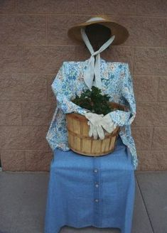 Set a basket in her lap, tucked gloves in her cuffs, and positioned arms around the basket. For the final touchI tucked a pair of rubber boots under her skirt peeking out a bit.  Or a witch for Halloween...