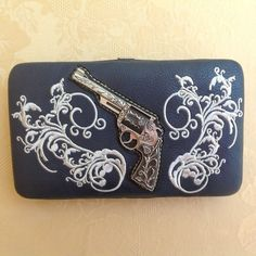 Montana West Western Pewter Pistol Wallet Brand new with tags. Navy Blue frame wallet adorned with gun metal pewter pistol with detailed engraving surrounded by white flower and vine embroidery. Lots of card and cash pockets. Removable checkbook cover. This wallet is a dark Navy Blue, Not BlackPlease ask all your questions before you purchase! I am happy to help! Sorry, no trades. Please, no lowball offers. Happy Poshing! Montana West Bags Wallets