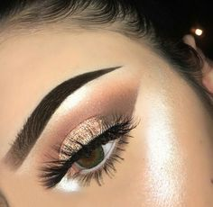 Clean and sharp eye makeup with brown shadows and glitter gold lids with winged liner and bold defined brows.