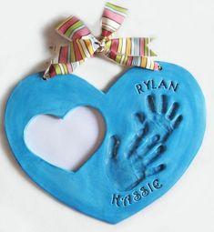 empreintes de mains bébé, cadeau fête des pères, pâte bleue en forme de coeur et ruban multicolore, un trou en forme de coeur