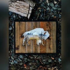 A cut out of a buffalo on reclaimed wood with a beautiful wheat field and trees in the distance painted within.