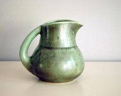Beautiful vintage Shearwater pottery pitcher by Peter Anderson has an amazing multitoned antique green glaze with charcoal. The pitcher is shape #10 and dates to about the 1940s.  The pitcher is rather squat with an elegant handle and a bit of a rustic look, with the beautiful charcoal over green glaze (my pictures dont do it justice). The inside is similarly glazed, and the bottom has the impressed quarter size Shearwater stamp.  The pitcher in very good condition, with excellent color…