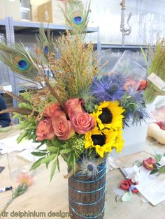 Country Chic Style Arrangement. Love the Peacock Feathers and sun flowers! Now this is too perfect for a Fergus farm wedding