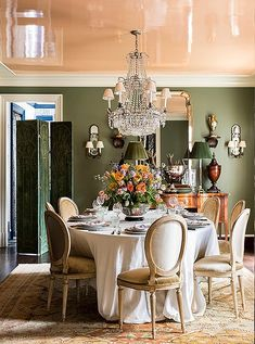 """Louis XVI chairs dressed in velvet encircle a table crowned by an antique chandelier. The combination of the apricot-lacquered ceiling and the dusty green walls creates a flattering glow. """"In the evening, the light that's reflected is just magic,"""" Danielle says. """"It's like liquid candlelight."""""""