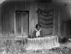 A woman weaves a cloak, with the work strung between two turuturu (pegs). On the wall behind her hangs a completed piupiu (unwoven flax skirt). Flax Weaving, Weaving Art, Hand Weaving, Maori Patterns, Polynesian People, Types Of Weaving, Maori Designs, Maori Art, Kiwiana