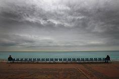 """""""Ein regnerischer Tag an der französischen Mittelmeerküste in Nizza. Ob diese zwei Meergucker gerade einen Konflikt aussitzen? Oder sind sie Fremde, die einfach allein den Blick auf Wolken und Meer genießen wollen? So kalt, dass man unbedingt enger zusammenrücken muss, ist es jedenfalls nicht - zum Zeitpunkt der Aufnahme lag die Temperatur bei neun Grad Celsius."""""""