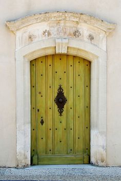 Love this yellow door with copper studs and the beautiful doorknob in the middle!