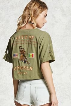 """A knit top featuring a split neck, short cuffed sleeves with roll-up tab details, a raw-cut rolled hem, and embroidered tiger and flag back patches with a """"City of Angels 69-70"""", and """"Back By Popular Demand / Worldwide Babes Club / Los Angeles Chapter / Local #1982"""" graphics."""