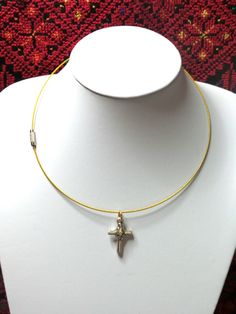 Yellow cable necklace with a silver cross.