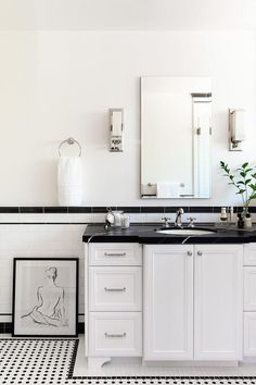 Stylish white and black bathroom boasts white and black vintage floor tiles placed framing a white bath vanity donning polished nickel hardware and contrasted with a honed black marble countertop.