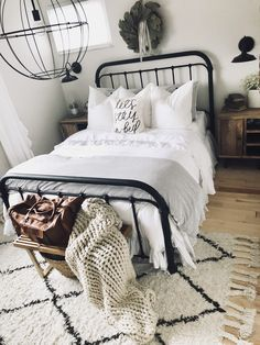 Farmhouse black metal bed with black farmhouse sconces, large knit blanket, tassel rug, leather weekend bag, ruffled comforter, fluffy bedding, wood nightstands, and a magnolia wreath!