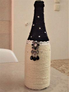 בקבוק מקושט בחוטי סריגה בצבעים לבן וכחול כהה עם תחרה לבנה וקישוט