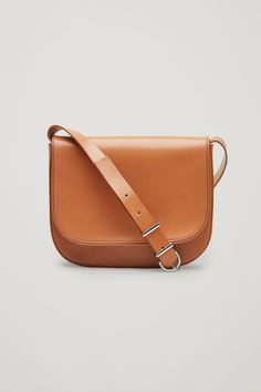 This shoulder bag is made from long lasting leather with smooth, rounded corners and piping details. It is completed with cotton lining, an adjustable metal buckle strap and a flap with a hidden magnetic fastening.
