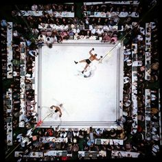 """Muhammad Ali vs. Cleveland Williams at the Astrodome, Houston, 1966 -  Neil Leifer:  """"I think this is the best picture I ever made. It's the only picture of mine that I have in my home. I could go on for a long time about the technical aspects of the shot, how I studied the Astrodome, planned the photo for weeks before the fight, pictured the shot in my head, rigged up the remote trigger that I used to get the shot from above while I was physically down at ringside shooting the fight — but what makes this so special to me is that it's as close as I've ever gotten to a perfect shot. Ali, Williams, the referee, the reporters, the symmetry, the drama — it's the one photograph I've taken where, looking back, I'd change nothing.""""     NOTE: Leifer is visible here, wearing a light blue shirt and seated near the top along the left-hand side of the ring, with his camera resting in front of him. Neil Leifer is a photographer for Sports Illustrated."""