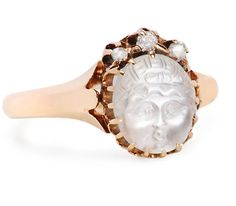 "Carved moonstone rings were quite popular during the later decades of the Victorian and earlier years of the Edwardian periods. The ""Man in the Moon"" motif was the most frequent image carved with classical representations also being employed.   Here we have a charming variation on those themes with the rendering of the face of a baby of Victorian times complete with chubby cheeks, wide open eyes, a baby nose and puckered lips. The wee lass is dressed in a bonnet and sports a bow. An oval ..."