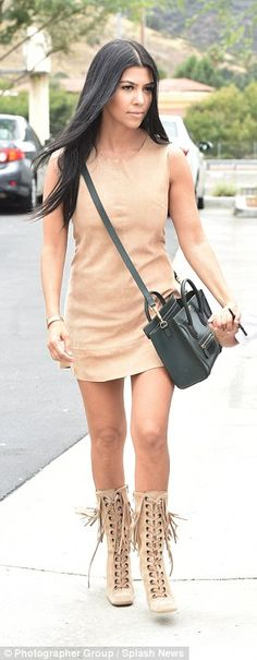 Ready to mingle: Kourtney looked fantastic in a beige shift dress and matching fringed boo...