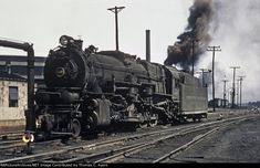 """East Altoona, Pennsylvania, c. 1952. Shown here is Pennsylvania Railroad engine #4335, an I-1SA (2-10-0) """"Decapod"""" built by the Baldwin Locomotive Works as an I-1S during December of 1922, rebuilt in Juniata as an I-1SA in January of 1943, and retired in October of 1959. The tall smoke stack in the background belongs to the Power House associated with the East Altoona Roundhouse, partially visible at the far left."""