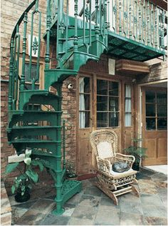 Outdoor wrought iron spiral staircase with decorative steps, painted green