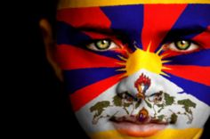 Portrait of a boy with flag of Tibet on his face