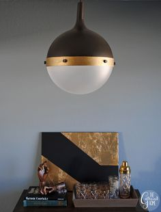 """This makeover was inspired by Thomas O'Brien's Hicks pendant light. The black upper, gold trim, and """"rivet"""" detail channel the original quite nicely. See more at The Gathered Home »   - HouseBeautiful.com"""