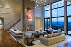 Ultra modern two story living room stands below a full glass facade overlooking a forested valley at right. Tile flooring sits several steps down from hardwood upper level at left. Central stone fireplace surround reaches toward the detailed ceiling.