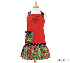 #burtonandburton Adult hand-painted Merry Christmas Y'all red apron with black and white polka dot ribbon ties.  Flirty skirt with various size red and green polka dots with swirls between.  Has matching pocket and is 65% polyester and 35% cotton